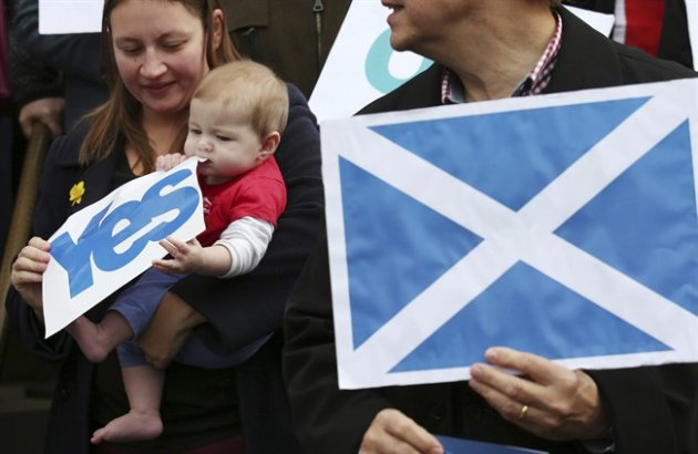 Caitlin Tierney chews a YES banner (AP Photo/ Andrew Milligan/PA Wire)