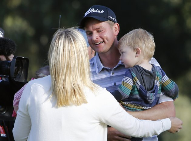 Merrick of the U.S. holds his son Chase and hugs his wife Jodi after winning the Northern Trust Open golf tournament on the second playoff hole at Riviera Country Club in Los Angeles