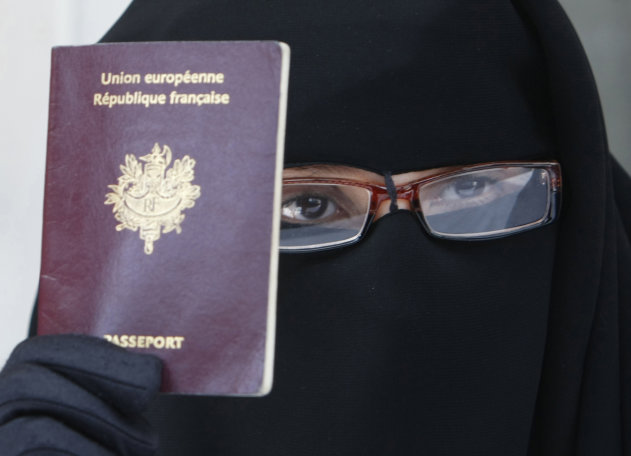 FILE - This May 18, 2010 file photo shows a woman, who gave her name as Najat, holding her passport during a press conference in Montreuil, east of Paris. The European Court of Human Rights on Tuesday, July 1, 2014, upheld France's law banning face-covering Muslim veils from the streets, in a case brought by another woman who claimed her freedom of religion was violated. (AP Photo/Remy de la Mauviniere, File)