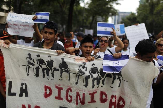 Migrants yell slogans as they hold up flags from Honduras, El Salvador and Guatemala, during a march in Mexico City