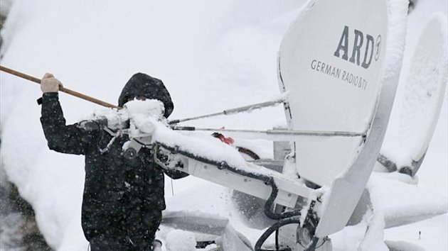A man clears snow off satellite dishes before the Women's World Cup Super Giant skiing race in Val d'Isere, French Alps (Reuters)