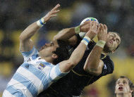 Argentina's Martin Rodriguez, left, and Scotland's Sean Lamont leap to take a catch during their Rugby World Cup Pool B match at the Wellington Regional stadium, New Zealand, Sunday, Sept. 25, 2011. (AP Photo/Natacha Pisarenko)