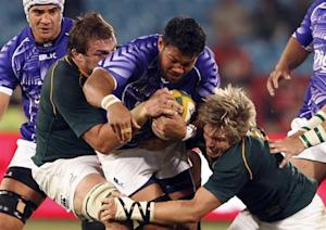 Samoa's Ofisa Treviranus is challenged by Flip van der Merwe and captain Jean de Villiers of South Africa during the test match at Loftus Versfeld in Pretoria