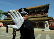 A Chinese policeman blocks photos being taken outside Zhongnanhai which serves as the central headquarters for the Communist Party of China after the sacking of politician Bo Xilai from the countries powerful Politburo, in Beijing on April 11, 2012