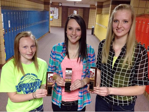 This April 14, 2014 photo, Lac qui Parle Valley High School girls basketball team members, Kelsea Lund, left, Alaysia Freetly and Kaitlin Connor holds their pieces of the MVP plaque in Madison, Minn.