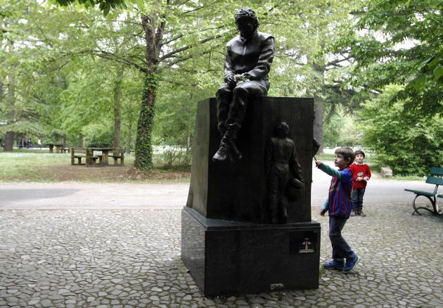 Children play next to the memorial statue of Formula One Brazilian driver Ayrton Senna in the park inside the race track at Imola
