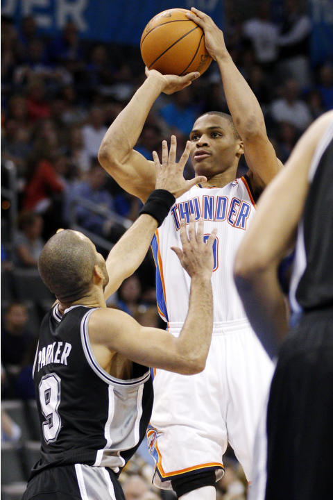 FILE - In this March 16, 2012, file photo, Oklahoma City Thunder guard Russell Westbrook, right, shoots over San Antonio Spurs guard Tony Parker (9), of France, in the third quarter of an NBA basketba