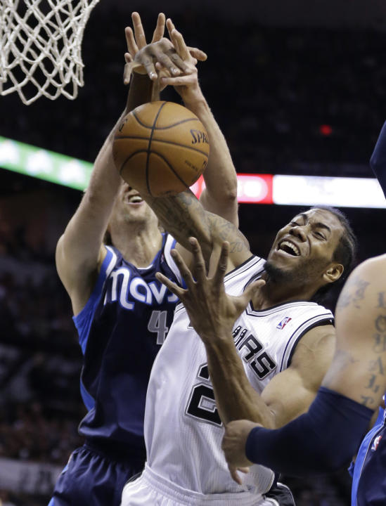 San Antonio Spurs' Kawhi Leonard (2) and Dallas Mavericks' Dirk Nowitzki, left, of Germany, fight for a rebound during the first half of Game 2 of the opening-round NBA basketball playoff seri