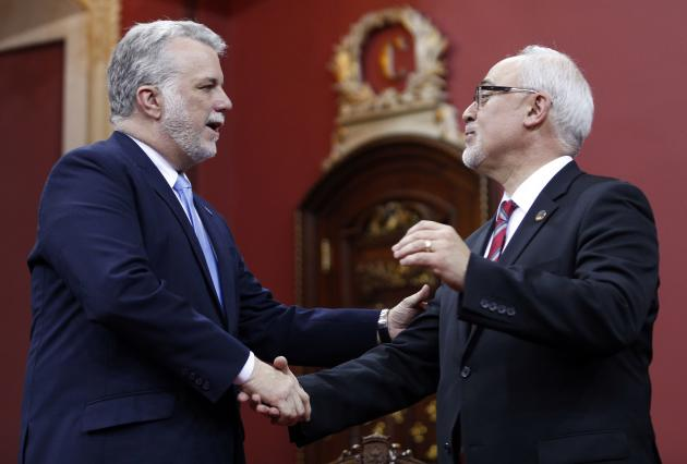 Quebec's Minister of Finance Carlos Leitao shakes the hand of Premier Philippe Couillard during a swearing-in ceremony at the National Assembly in Quebec City