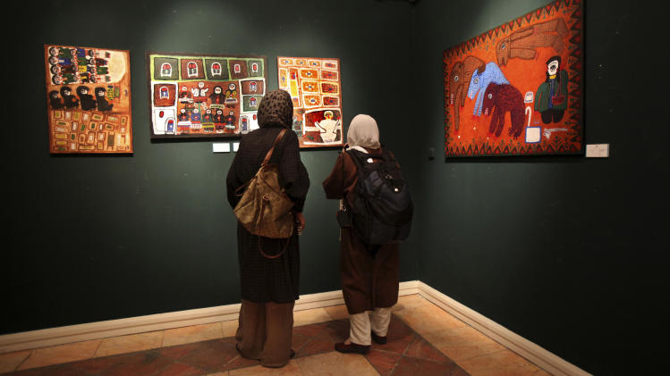 In this picture taken on Monday, July 1, 2013, two Iranian women look at paintings in an art gallery, in Tehran, Iran. (AP Photo/Vahid Salemi)