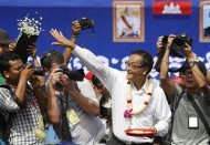 Sam Rainsy (C), president of the opposition Cambodia National Rescue Party (CNRP), throws flowers towards his supporters during a protest at the Freedom Park in Phnom Penh September 15, 2013. REUTERS/Samrang Pring