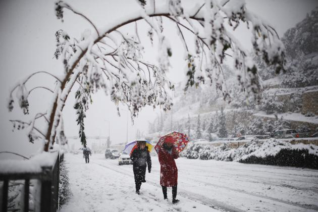 Women walk with umbrellas on a snow-covered road during winter in Jerusalem