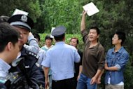 "Chinese police prepare to detain protesters from a group who attempted to unfurl a protest banner outside the Philippines embassy in Beijing, on May 12. One briefly held up a sign reading: ""Philippine servants, get away from Huangyan Island"" using the Chinese name for the Scarborough Shoal"