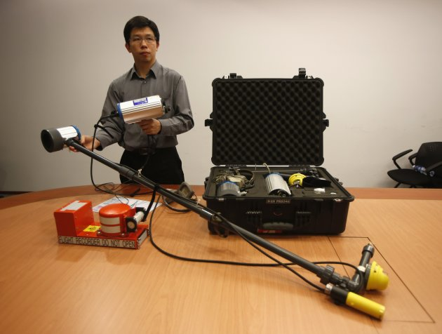 A specialist from Singapore's Ministry of Transport's Air Accident Investigation Bureau (AAIB) showcases a set of underwater locator beacon detector that will be used to assist in locating the flight recorders of the missing AirAsia flight QZ8501 plane, at Changi Airport in Singapore December 29, 2014. The missing AirAsia jet carrying 162 people could be at the bottom of the sea after it was presumed to have crashed off the Indonesian coast, an official said on Monday, as countries around Asia sent ships and planes to help in the search effort. REUTERS/Edgar Su (SINGAPORE - Tags: TRANSPORT DISASTER)