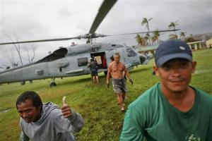 Survivor of Typhoon Haiyan gestures after receiving aid delivered by a U.S. military helicopter to a isolated village north of Tacloban