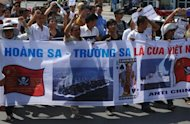 Vietnamese shout anti-China slogans and hold placards during a march towards the Chinese embassy in Hanoi on July 22, 2012. Beijing will establish a military garrison on a group of disputed islands in the South China Sea, China's defence ministry said Monday, a move likely to provoke further tensions with its neighbours