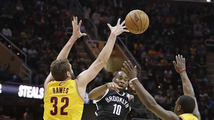 Brooklyn Nets' Marcus Thornton (10) passes over Cleveland Cavaliers' Spencer Hawes (32) and Dion Waiters (3) during the first quarter of an NBA basketball game Wednesday, April 16, 2014, in Cleveland
