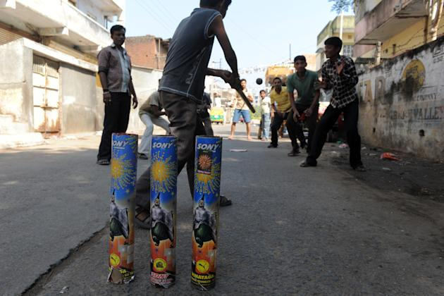 Indian youths play street cricket using