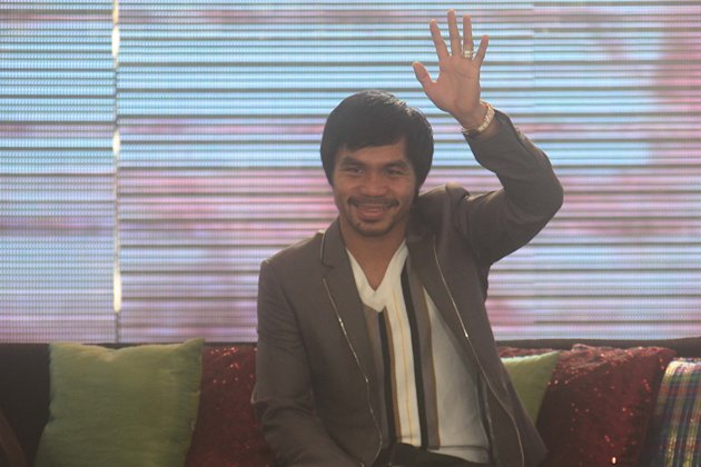 Manny Pacquiao waves at his fans during a homecoming event prepared by GMA Network (George Calvelo/NPPA Images)