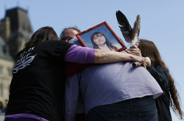 "A photograph of Terrie Ann Dauphinais is seen as participants hug after singing a song during the ""24 Hour Sacred Gathering of Drums"" protest calling for an inquiry into missing and murdered aboriginal women, on Parliament Hill in Ottawa May 12, 2014. Dauphinais was found murdered in her Calgary home on April 29, 2002 and the case remains unsolved. REUTERS/Chris Wattie (CANADA - Tags: POLITICS CIVIL UNREST)"