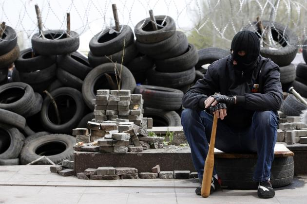 Pro-Russian protester wearing a balaclava and holding a baseball bat sits next to piles of bricks and tyres outside a regional government building in Donetsk