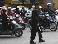 A police officer stands in a Hanoi street on December 4, 2012. Vietnam jailed two young activists Thursday for distributing anti-government leaflets, in a case slammed by rights groups as a fresh attempt by the communist regime to silence its critics