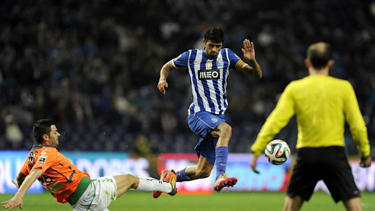 FC Porto's Lucho Gonzalez, from Argentina, drives the ball past Vitoria Setubal's Daniel Soares, left, in a Portuguese League soccer match at the Dragao Stadium in Porto, Portugal, Sunday, Jan. 19, 2014. Porto won 3-0