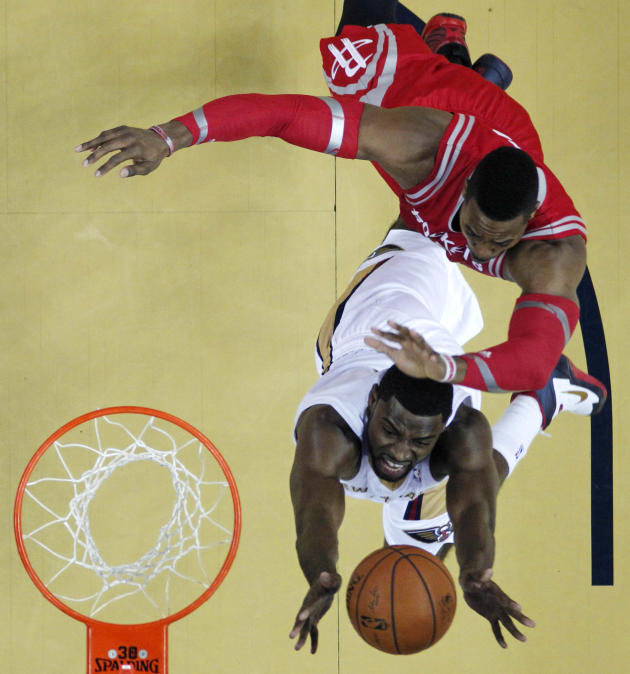 New Orleans Pelicans forward Tyreke Evans goes to the basket against Houston Rockets center Dwight Howard, top right, in the first half of an NBA basketball game in New Orleans, Wednesday, April 16, 2