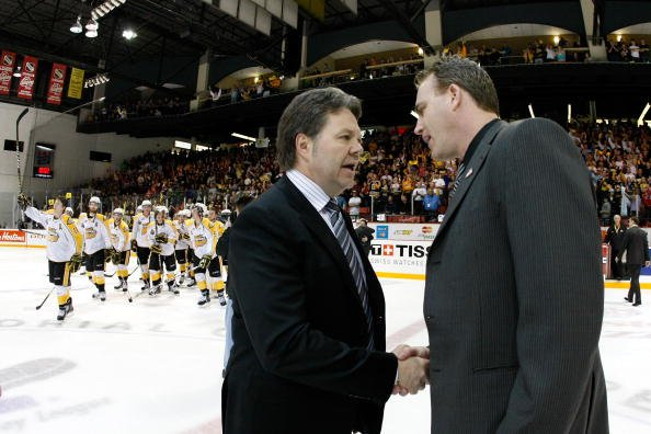 BRANDON, CANADA - MAY 21: (L-R) Brandon Wheat Kings Head Coach Kelly McCrimmon shakes hands with Calgary Hitmen Head Coach Mike Williamson after the Wheat Kings defeated the Hitmen in overtime during the 2010 Mastercard Memorial Cup Tournament at the Keystone Centre on May 21, 2010 in Brandon, Manitoba, Canada. The Wheat Kings defeated the Hitmen 5-4 in overtime. THe Wheat Kings will face the Spitfires in the Finals. (Photo by Richard Wolowicz/Getty Images)