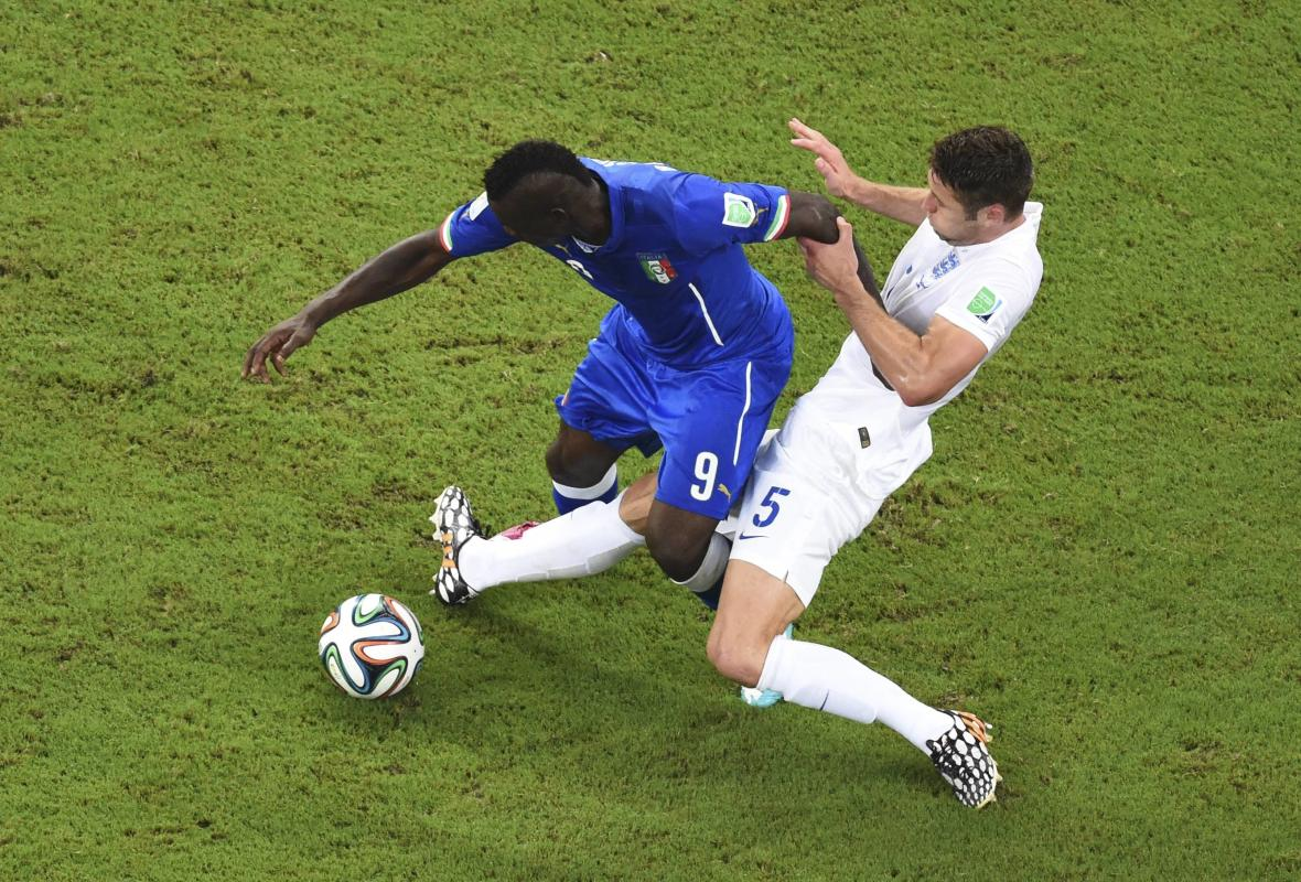 Italy's Balotelli fights for the ball with England's Cahill during their 2014 World Cup Group D soccer match at the Amazonia arena in Manaus