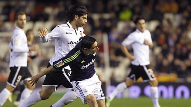 Valencia's Ever Banega (L) and Real Madrid's Angel Di Maria fight for the ball (Reuters)