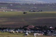 A military helicopter patrols the area as the hearse carrying the coffin of former South African President Nelson Mandela is escorted by a funeral procession after entering his home in Qunu, Eastern Cape December 14, 2013. REUTERS/Siegfried Modola