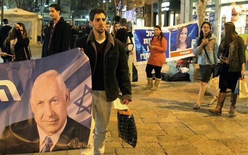 A supporter of the Likud party holds a banner showing Israeli Prime Minister and party leader Benjamin Netanyahu, on January 21, 2013 at the Ben Yehuda Mall in Jerusalem. Israelis vote Tuesday in a general election expected to return Netanyahu to power at the head of a government of hardline right-wing and religious parties.