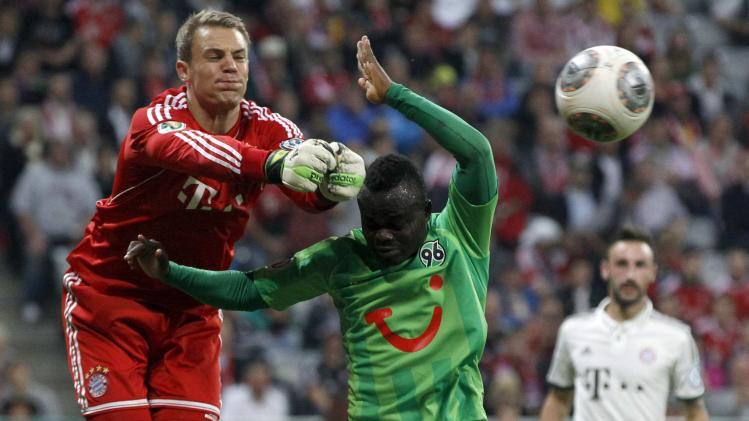 Bayern Munich's goalkeeper Neuer saves ball against Konan of Hanover 96 during German soccer cup match in Munich