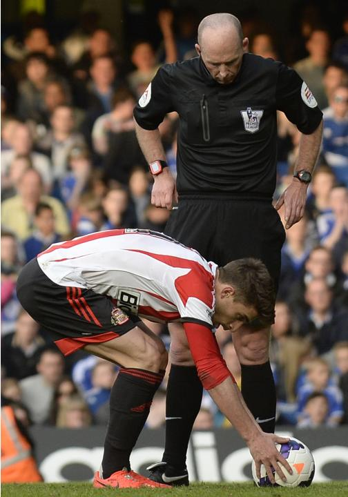 Referee Dean watches Sunderland's Borini place the ball for a penalty against Chelsea during their English Premier League soccer match in London