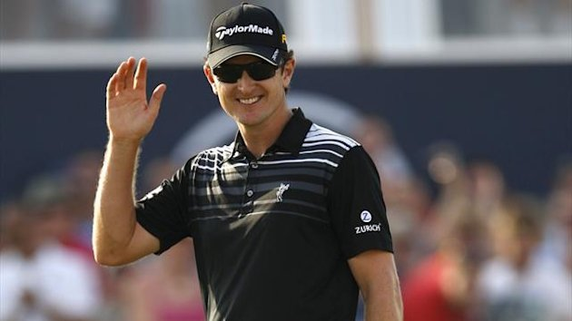 Justin Rose of Britain waves to the public after putting on the 18th hole during the final round of the DP World Tour Championship at Jumeirah Golf Estates in Dubai