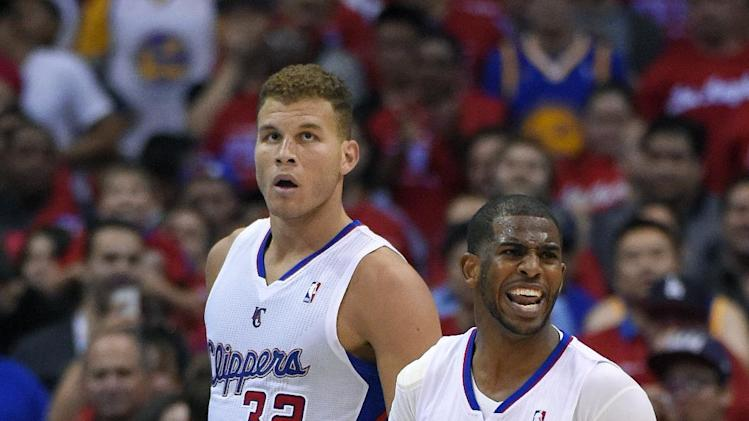 Los Angeles Clippers guard Chris Paul, right, reacts to a foul as forward Blake Griffin looks on during the second half in Game 1 of an opening-round NBA basketball playoff series against the Golden State Warriors, Saturday, April 19, 2014, in Los Angeles. The Warriors won 109-105