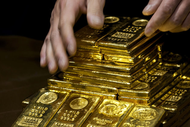 A staff member displays gold bullion bars during a news conference at the Chinese Gold and Silver Exchange Society in Hong Kong.