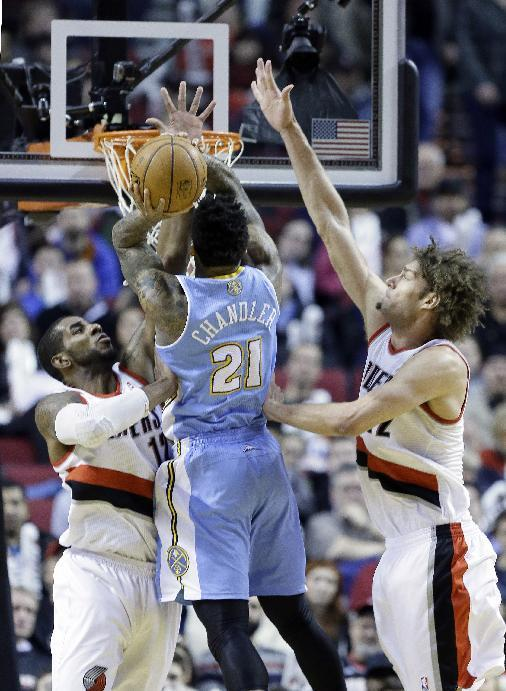 Portland Trail Blazers forward LaMarcus Aldridge, left, and Trail Blazers center Robin Lopez, right, defend Denver Nuggets forward Wilson Chandler as he shoots during the second half of an NBA basketball game in Portland, Ore., Thursday, Jan. 23, 2014.  Portland beat Denver 110-105
