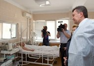 Ukrainian President Viktor Yanukovych speaks with a hospital patient in the Ukrainian city of Dnipropetrovsk. Yanukovych visited Ukraine's industrial heartland after a wave of blasts injured dozens of people ahead of the Euro 2012 football tournament