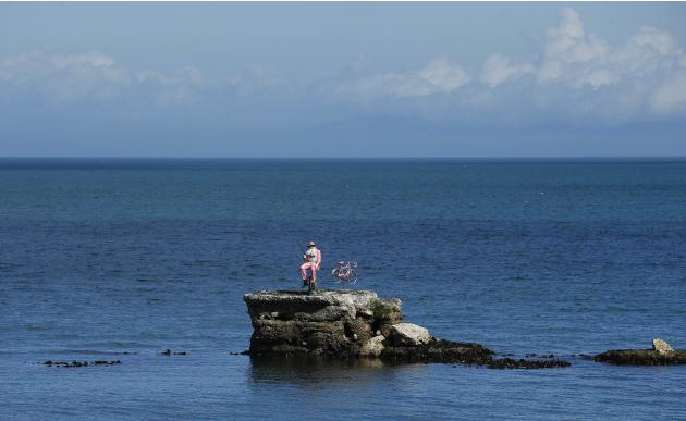 A model of a pink fisherman and bicycle are positioned on a rock in the Irish Sea near the village of Waterfoot