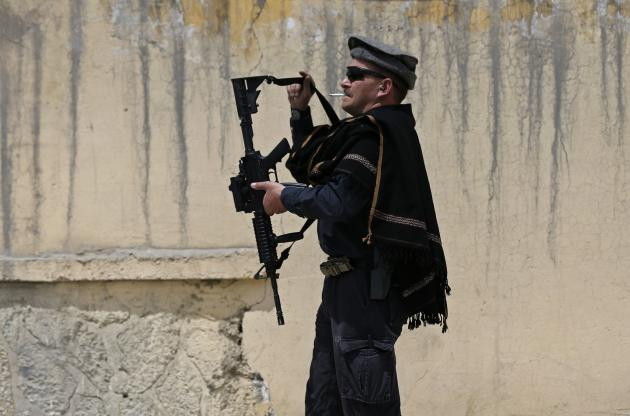 A foreign security guard prepares his weapon at the gate of Cure Hospital after three Americans were killed in Kabul