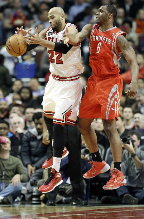 Chicago Bulls forward Taj Gibson, left, tries to catch a pass against Houston Rockets forward Terrence Jones during the first half of an NBA basketball game in Chicago on Thursday, March 13, 2014