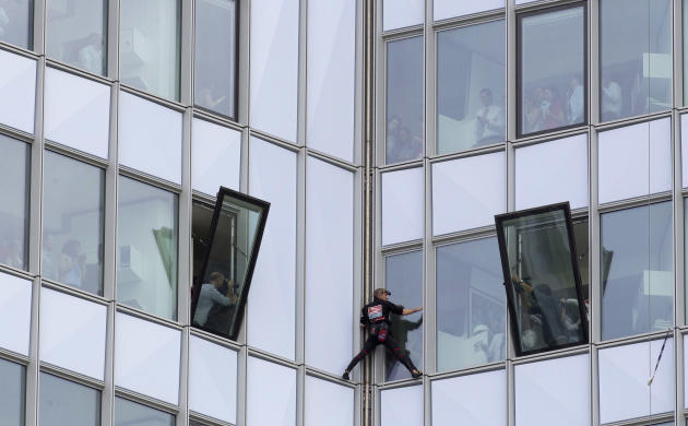 People look out of their windows as French urban climber Alain Robert, known as 'Spiderman', climbs up the 231 meter high (758 feet) First Tower, the tallest skyscraper in France, in the La De