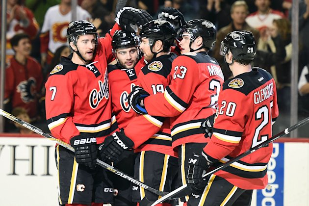 Dec 6, 2014; Calgary, Alberta, CAN; Calgary Flames defenseman Mark Giordano (5) (second from left) celebrates his first period goal against the San Jose Sharks at Scotiabank Saddledome. (Candice Ward-USA TODAY Sports)