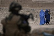 A French soldier watches two Afghan women walk between Nijrab and Tagab in Kapisa region. A Taliban suicide bomber wearing a burqa killed four French soldiers and wounded five others Saturday in an attack on a NATO-led patrol in eastern Afghanistan, officials said