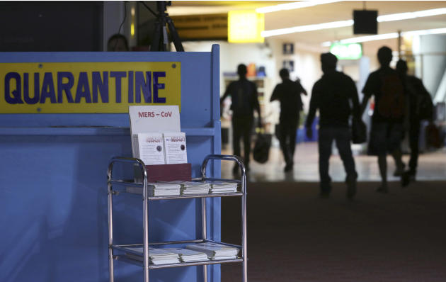 FILE - In this Wednesday, April 16, 2014, file photo, passengers walk past the medical quarantine area showing information sheets for the Middle East respiratory syndrome coronavirus at the arrival se