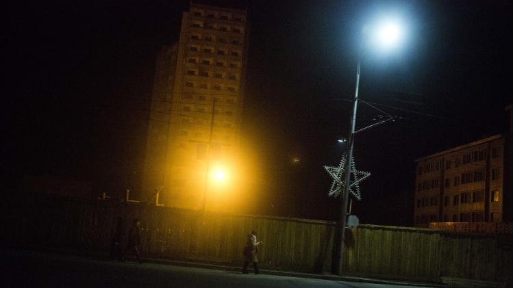 North Korean pedestrians walk along a nighttime street in central Pyongyang, North Korea on Thursday, Feb. 21, 2013. (AP Photo/David Guttenfelder)