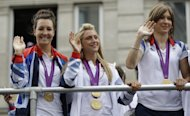 Britain's cyclist Laura Trott, center, waves to the crowds as the Team GB Olympic and Paralympic teams parade in the streets of London, Monday, Sept. 10, 2012. Our Greatest Team Parade, the procession of athletes, celebrates the achievements of British Olympians and Paralympians at the London 2012 Games. (AP Photo/Lefteris Pitarakis)