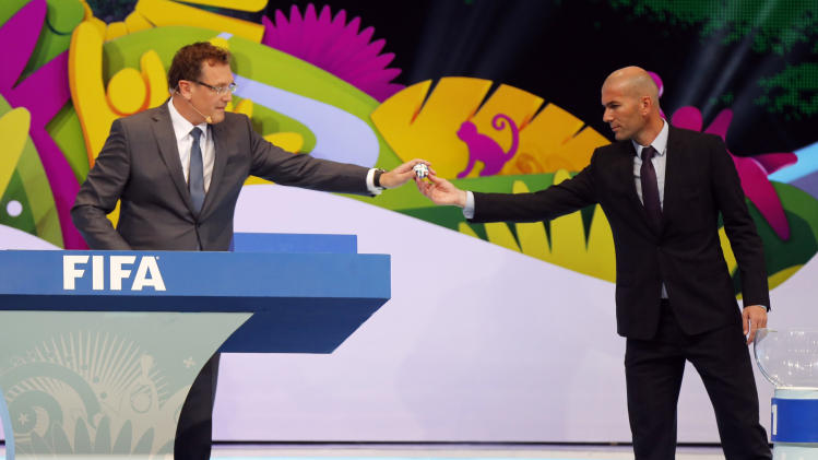 Former France soccer player Zinedine Zidane hands a ball that he had drawn from a pot to FIFA Secretary General Jerome Valcke during the draw for the 2014 World Cup at the Costa do Sauipe resort in Sao Joao da Mata